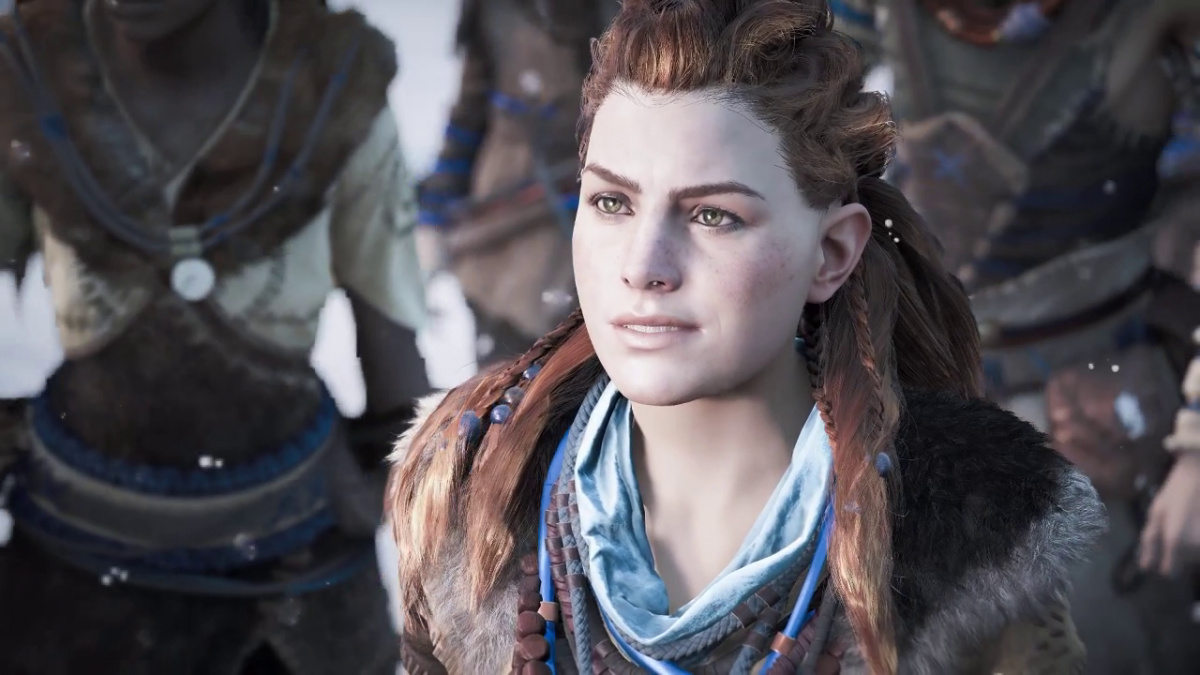 A screenshot of Aloy. She has long, red hair and a blue scarf. She is giving a half smile and looking towards an off-screen speaker.