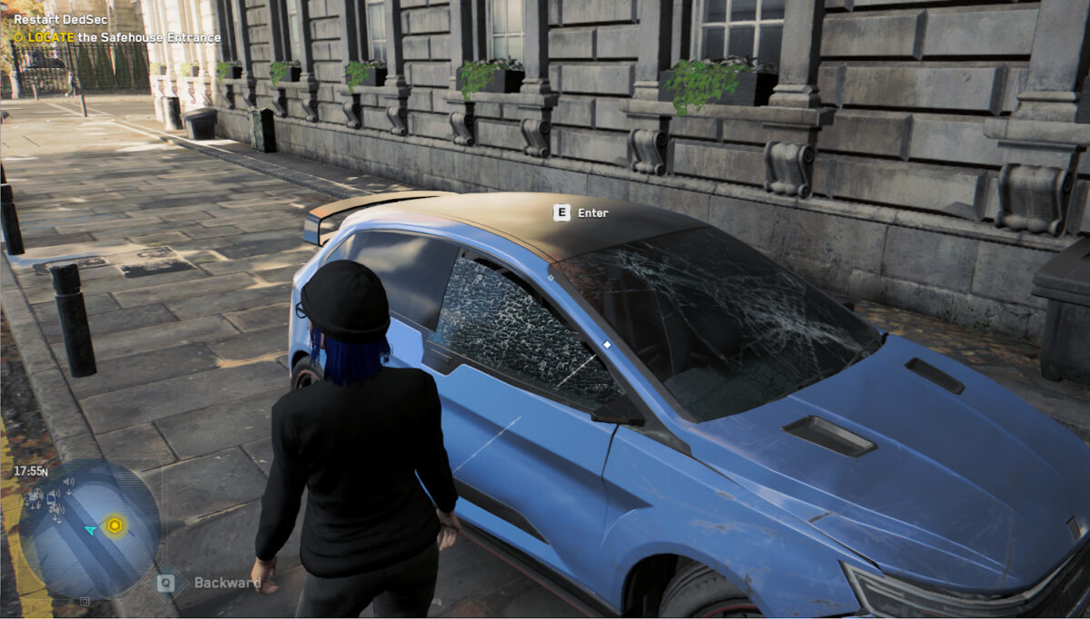 A user standing in front of a blue car, which has a broken windshield, is missing its mirrors, and the passenger window is busted. It took a nice beating.