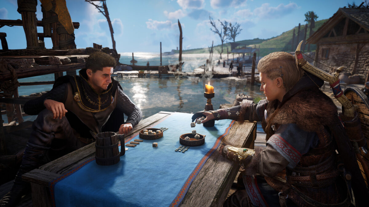 A man and woman sitting by the side of a lake on a dock, playing dice and drinking beer.