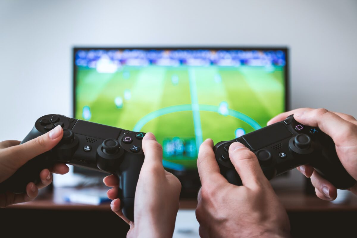Two people holding PlayStation controllers and playing a soccer game.