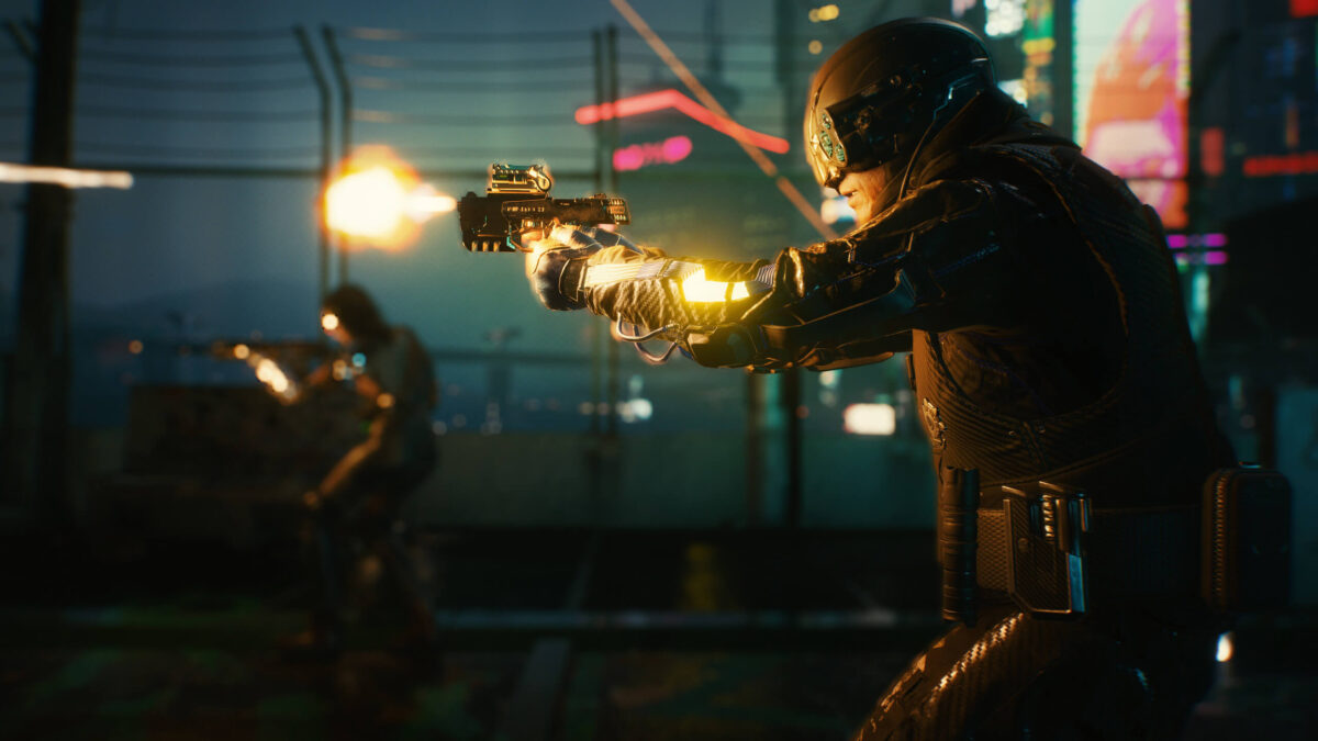 A man in  futuristic battlegear shooting an advanced, colorful pistol and a nearby enemy. The scene is dark, with bright neon colors vibrating from signs in the background.